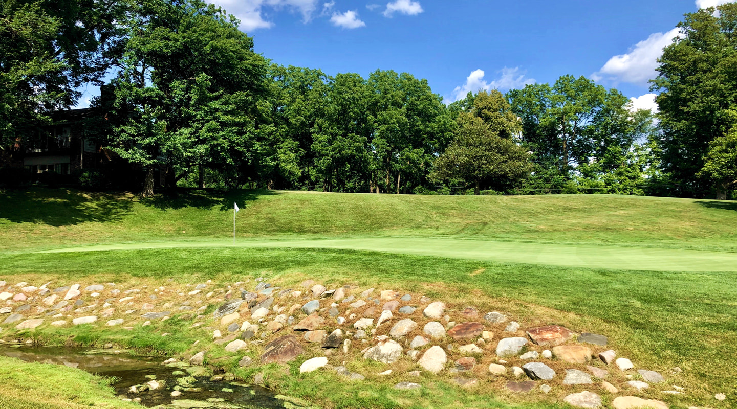 A rocky bank fronts the green at the 13th
