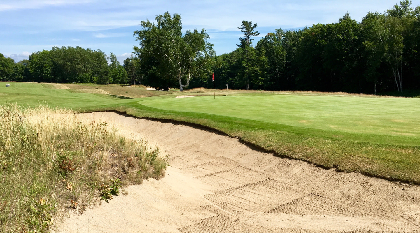 Bunkers lurk around the green on the short 15th