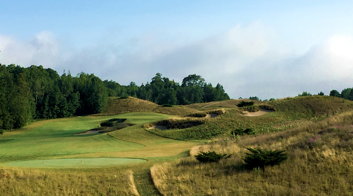 The hillside hides part of a wide fairway on the 8th