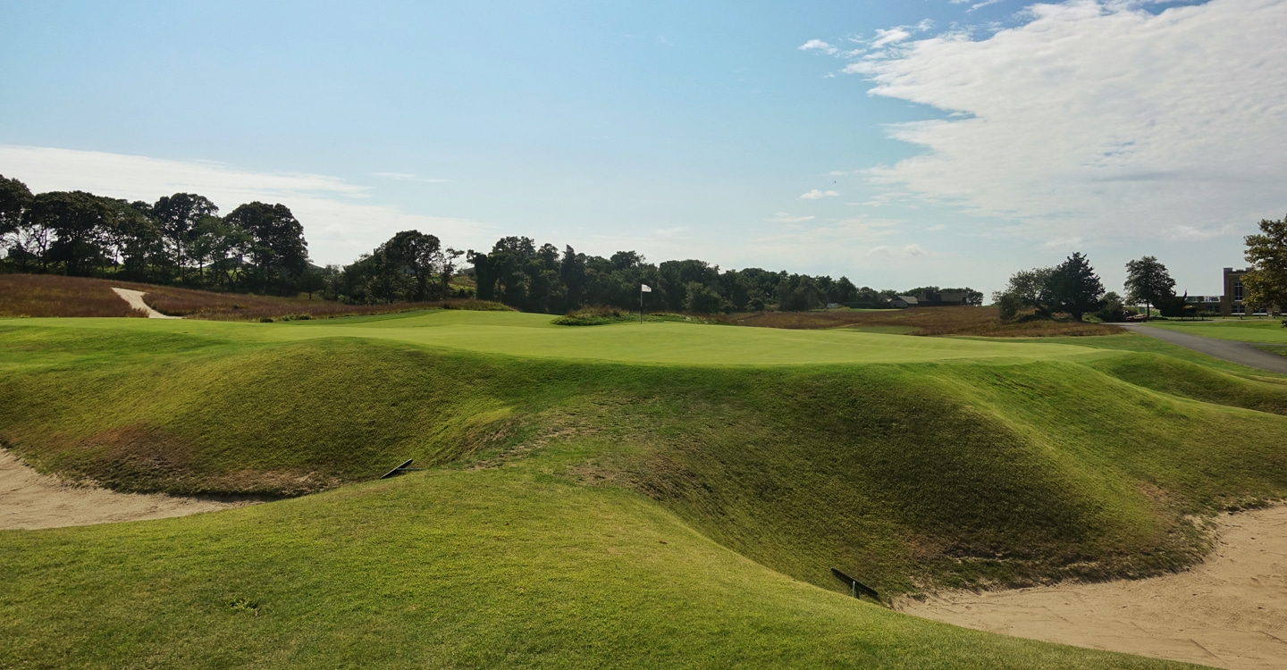 Deep bunkers guard the elevated green