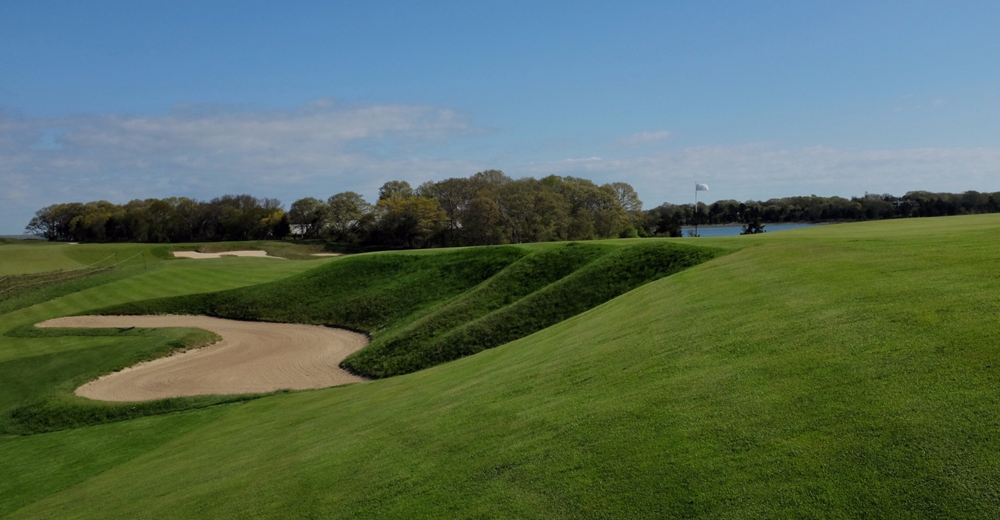 A deep bunker takes its traditional position in front
