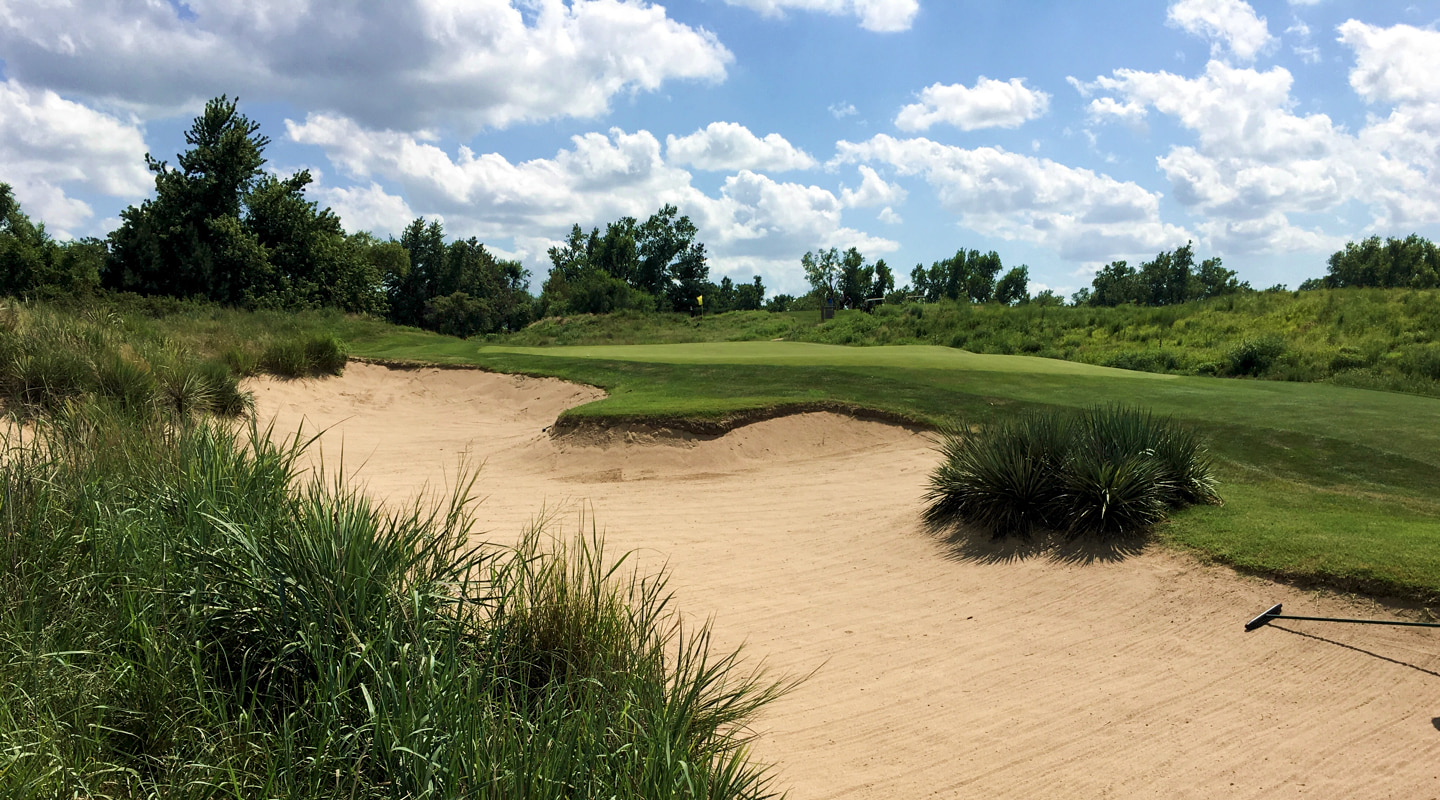 A deep bunker guards the green front left on the 17th