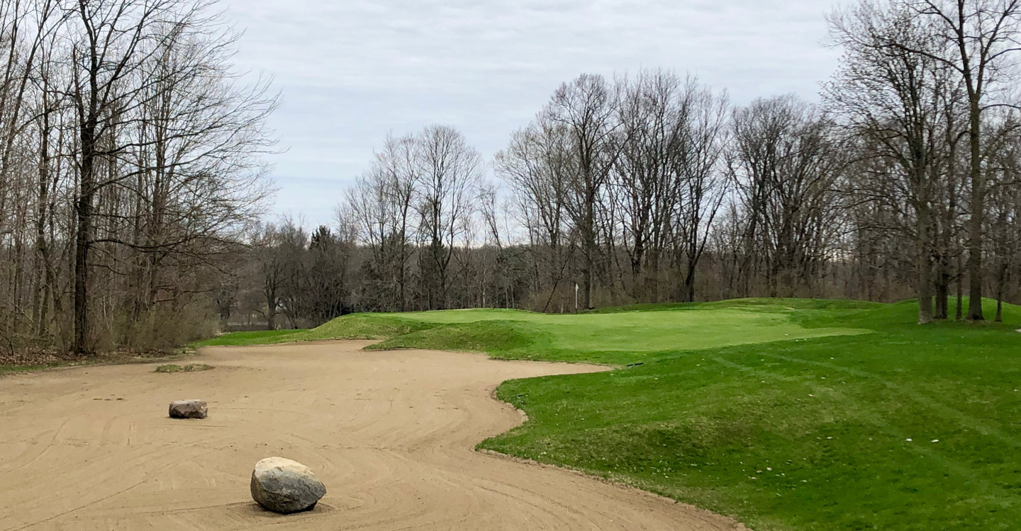 Large stones scattered in the bunker fronting the par-3 11th