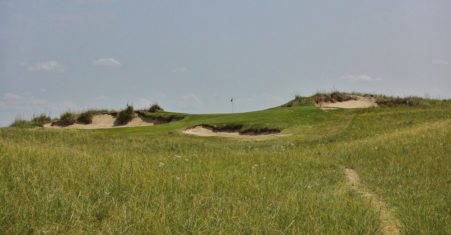 A flag, a false front and bunkers are all the player sees from the 17th tee
